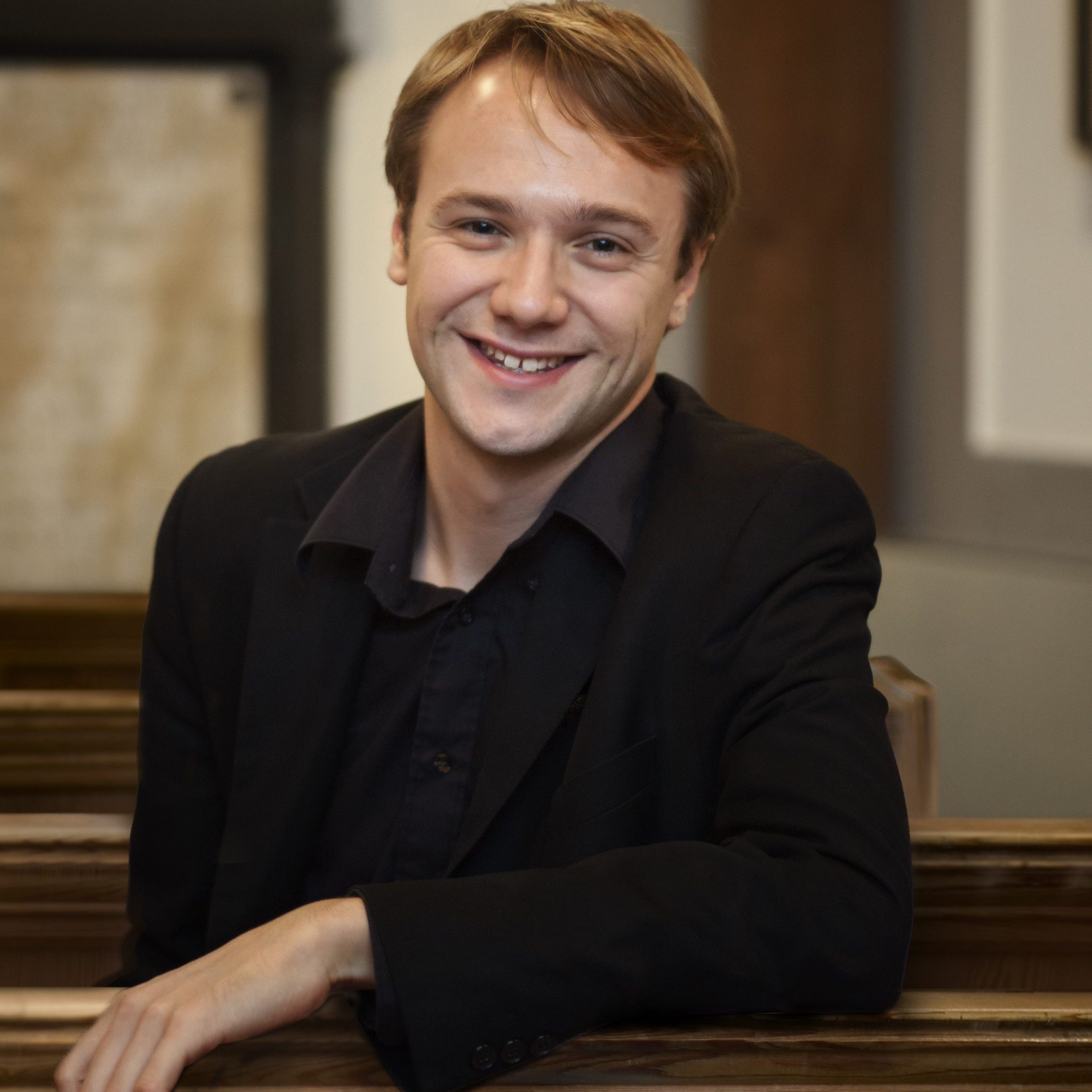 Relaxed man wearing all black, smiling at the camera